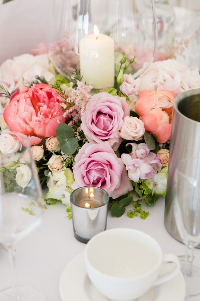 Table centres of coral flowers for a wedding